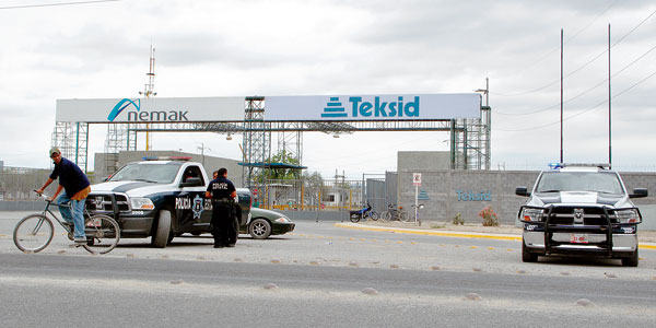 Cops guard the entrance to the Teksid plant in Mexico after workers downed tools.