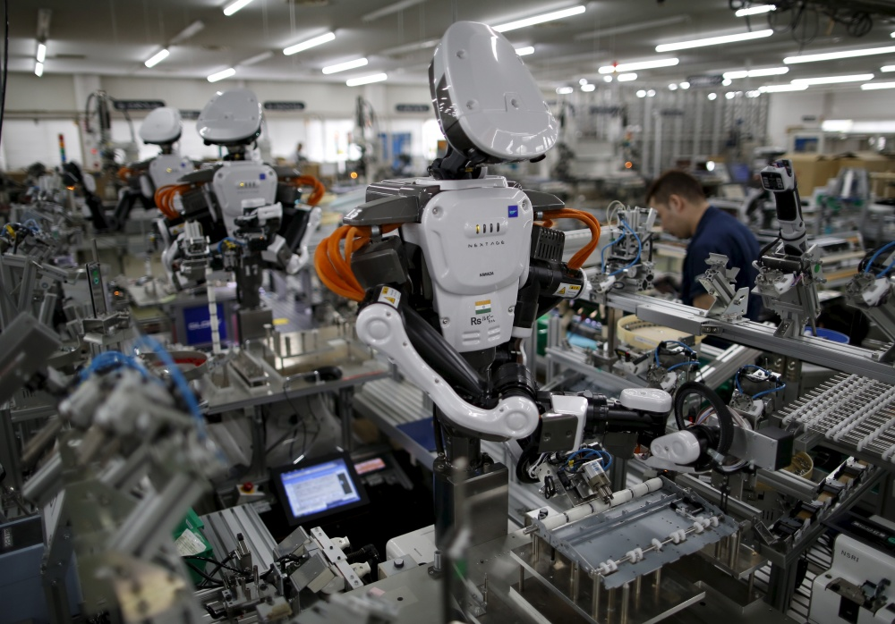 Humanoid robots work side by side with employees in the assembly line at a factory in Japan.